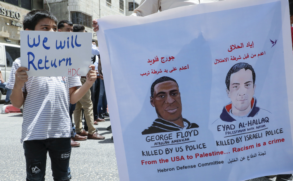 Palestinians lift banners protesting the killing of Eyad Hallaq, a Palestinian man with autism shot dead by Israeli police, and the case of George Floyd, an unarmed black man killed by policeman in the U.S., during a rally by supporters of the Fatah movement in the West Bank city of Hebron.