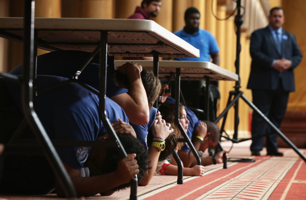 Volunteers participate in an earthquake drill during an event on earthquake preparedness October 14, 2014 at the National Building Museum in Washington, DC. Federal and local officials joined national experts to discuss earthquake preparedness and to provide details regarding the international Great ShakeOut day of action, an earthquake drill taking place on Thursday, October 16.