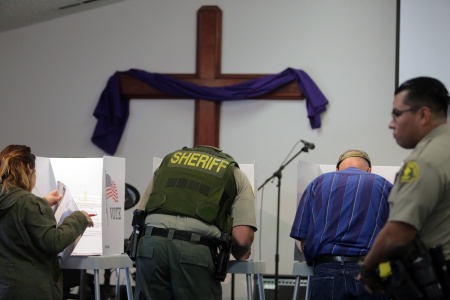A sheriff's deputy votes at a polling station at the Big Bear Christian Center in Big Bear, California, November 8, 2016.