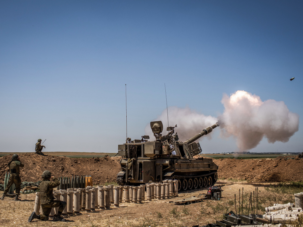 Israeli artillery fires towards Gaza Strip from a position at the Israeli-Gaza border near Sderot, on Wednesday.