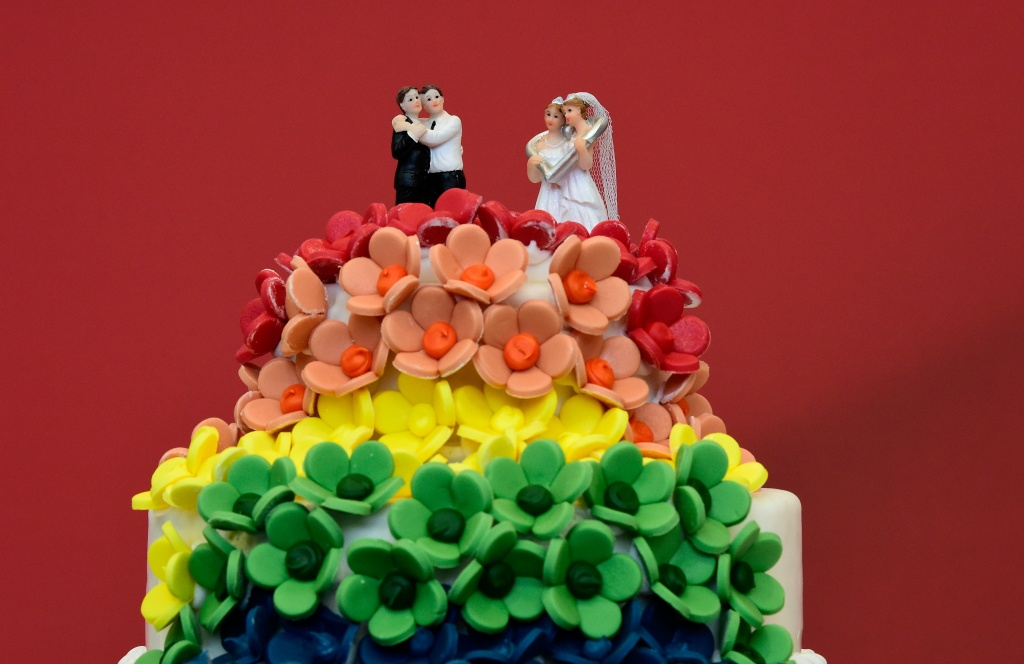 A wedding cake in rainbow colors and decorated with figurines of two women and two men is pictured in Berlin on June 30, 2017.