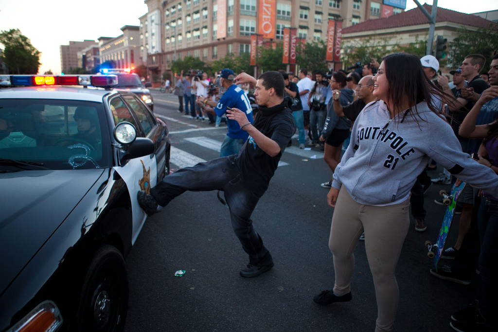 A protester kicks a passing police car during a demonstration to show outrage for the shooting death of Manuel Angel Diaz, 25, at Anaheim City Hall on July 24, 2012 in Anaheim, California. Diaz was fatally shot July 21 by an Anaheim police officer and has sparked days of protests by the angered community.