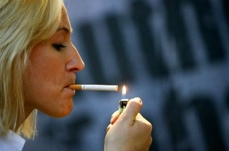 A woman lights a cigarette.