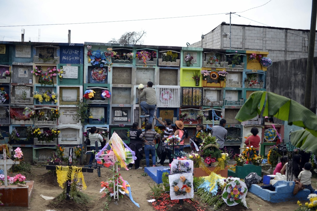 People adorn the resting place of relatives at the municipal cemetery of Villa Nueva, Guatemala during All Saints Day on November 1, 2016.