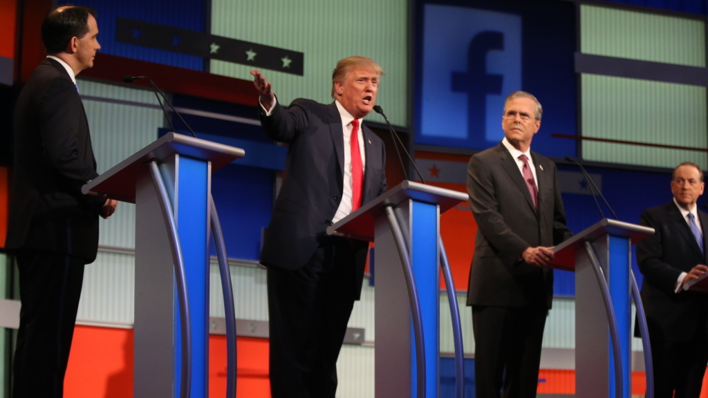 Republican presidential candidates from left, Scott Walker, Donald Trump, Jeb Bush and Mike Huckabee take the stage for the first Republican presidential debate.