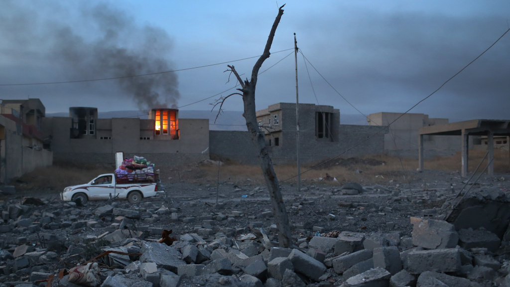 People remove household goods from the rubble as a house burns on Sunday in Sinjar, Iraq. Kurdish forces, with the aid of months of U.S.-led coalition airstrikes, liberated the town from ISIS.