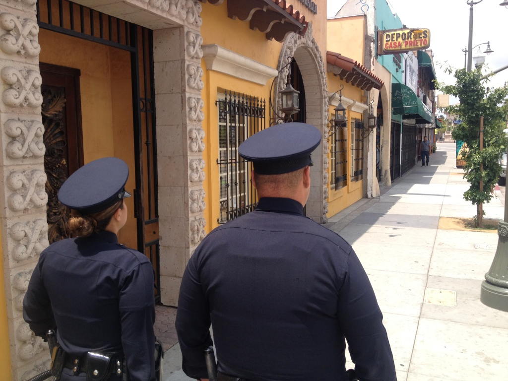 LAPD Officers Jennifer Aguilar (L) and Miguel Ruano walk down First Street in Boyle Heights.