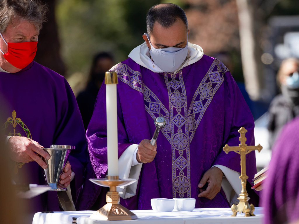 Rev. Michael Amabisco blesses ashes during Ash Wednesday service at St. Raymond Catholic Church in Menlo Park, Calif., in February. A new Gallup survey says those professing church membership has fallen 18% for Catholics since 2000.