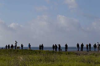 People line a hill overlooking the bay to watch as tsunami surges hit on March 11, 2011 in Half Moon Bay, California.