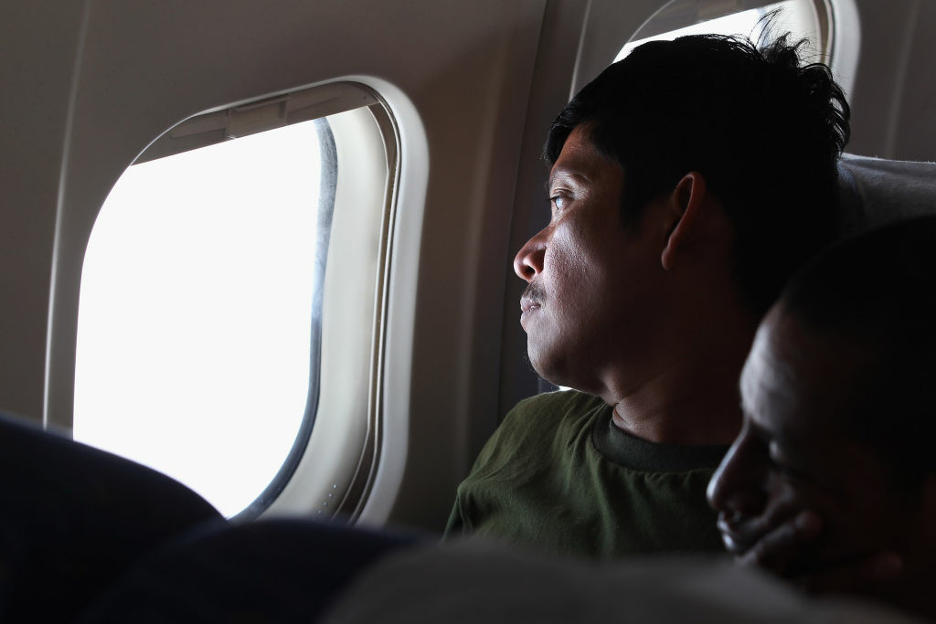 Undocumented Guatemalan immigrant Fidel Rodriguez looks out the window before landing on a deportation flight from Mesa, Arizona on June 24, 2011 in flight to Guatemala City, Guatemala. According to Pew, the number of immigrants entering the U.S. illegally remained unchanged from 2009 to 2012, but a shift was seen geographically — East Coast states saw gains, while states closer to the border, like California and Arizona, saw declines.