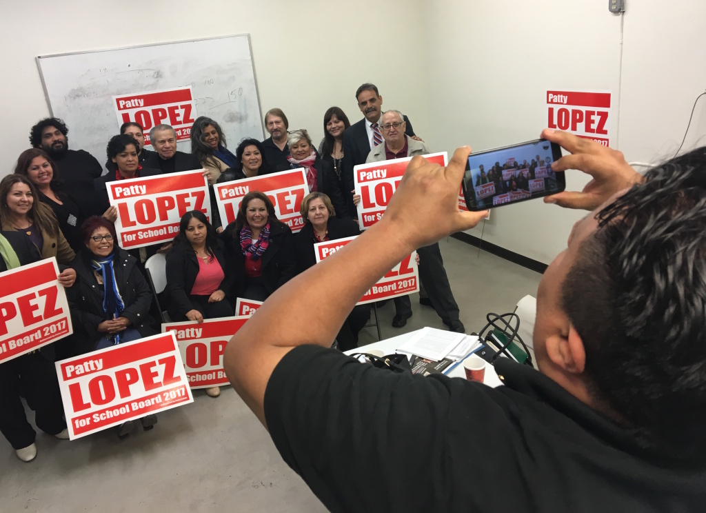 Saul Mejia snaps a photo of L.A. school board candidate Patty Lopez's supporters at a meeting in the community room of a Panorama City mall on Sunday, March 5.