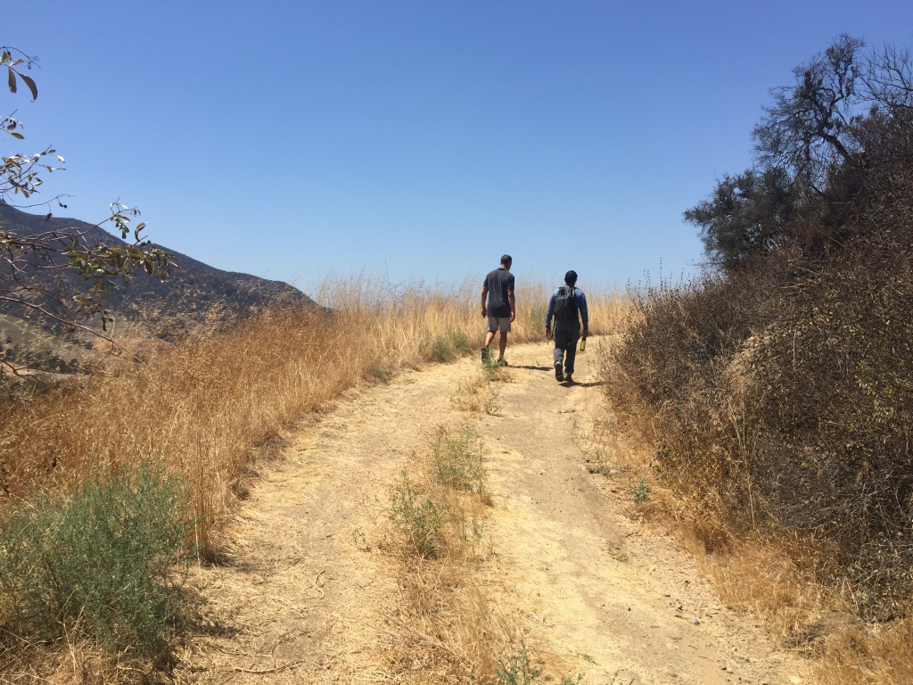 Miguel Ordeñana and A Martinez hike up to a wildlife camera in Griffith Park.