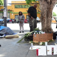 "People gather at a makeshift memorial for a homeless man, known by the name of ""Africa,"" who was shot and killed by LA police on March 2, 2015 in Los Angeles, California."