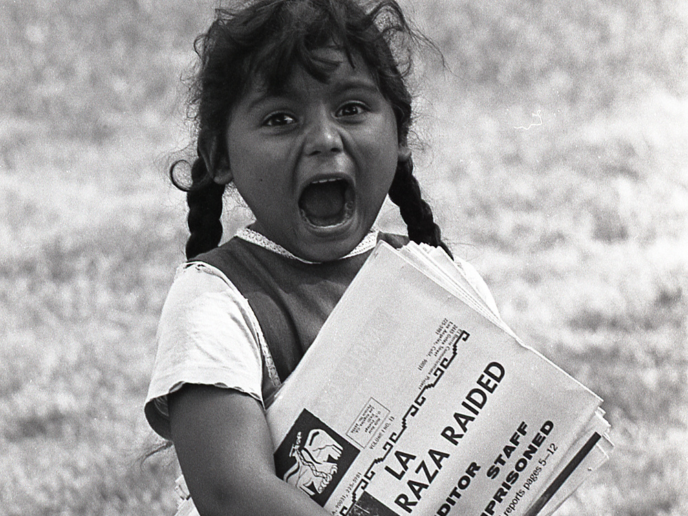 <em>A young Chicanita hawks </em>La Raza<em> newspapers at the Poor People's Campaign, Washington, D.C.</em> <em>May-July 1968.</em>