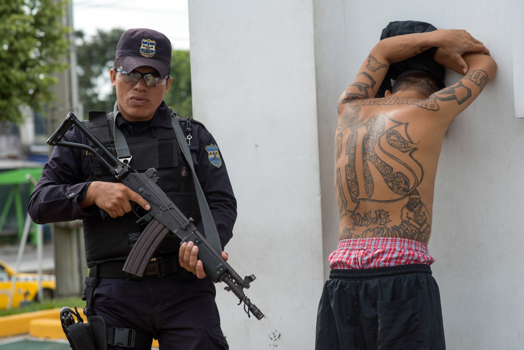 A policeman detains a suspected member of the MS-13 gang at a checkpoint in San Salvador during a ban on public transport imposed by the gangs.