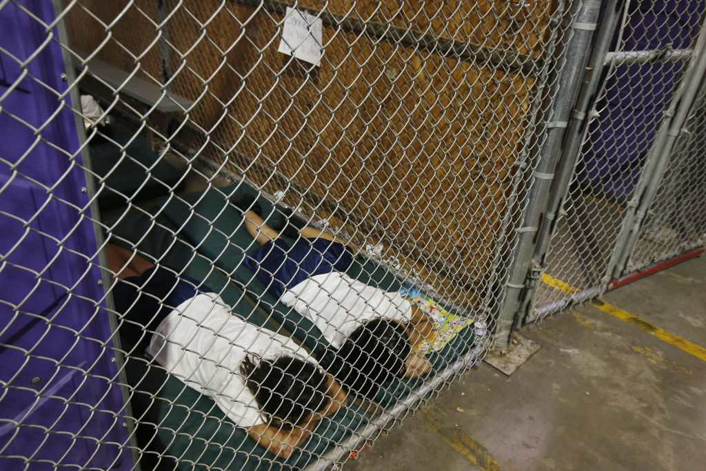 Two female detainees sleep in a holding cell, as the children are separated by age group and gender, as hundreds of mostly Central American immigrant children are being processed and held at the U.S. Customs and Border Protection Nogales Placement Center on June 18, 2014, in Nogales, Arizona.  Brownsville, Texas, and Nogales, have been central to processing the more than 47,000 unaccompanied children who have entered the country illegally since Oct. 1.