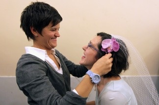 Danielle Peregory (L) places a veil on the head of her future wife Kelly Jones as they wait in line to get a marriage license at San Francisco City Hall August 12, 2010 in San Francisco, California.