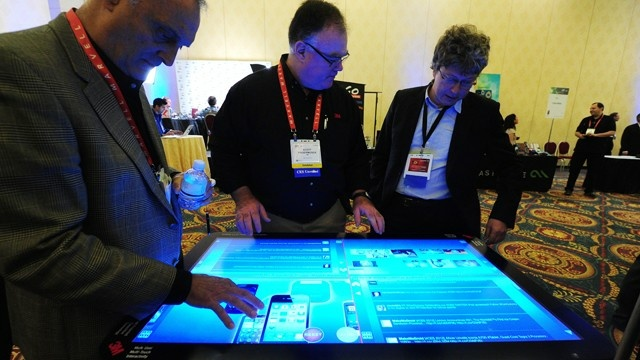 People sample a 3M Touch Systems 46-inch PCT-display demonstrating the scalability of projective capacitive technology at CES Unveiled, ahead of the opening of the annual Consumer Electronics Show, Jan. 8, 2012 in Las Vegas, Nevada.