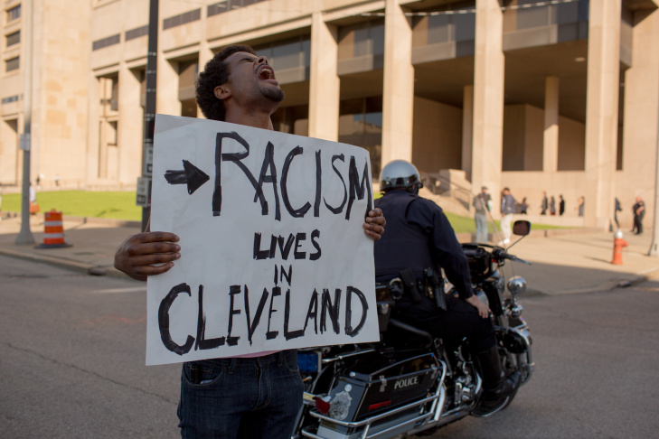 A protester is arrested after the acquittal of Michael Brelo, a patrolman charged in the shooting deaths of two unarmed suspects Saturday, May 23, 2015, in Cleveland. Brelo, who fired down through the windshield of a suspect's car at the end of a 137-shot barrage that left the two unarmed black occupants dead, was acquitted Saturday of criminal charges by a judge who said he could not determine the Cleveland officer alone fired the fatal shots.