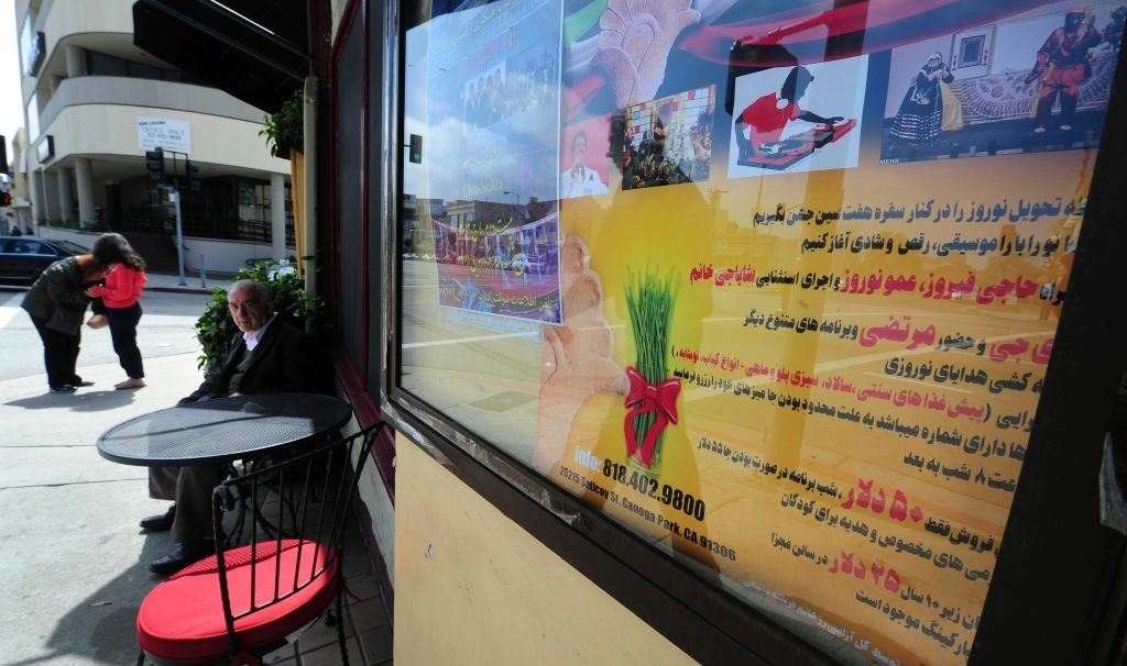 A man sits outside a cafe beneath where a sign which reads