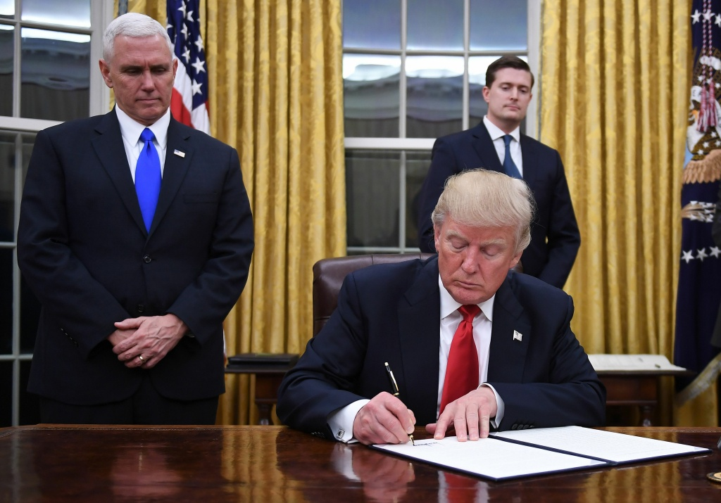 File: President Donald Trump signs an executive order as Vice President Mike Pence looks on at the White House in Washington, D.C. on Jan. 20, 2017.