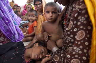 Exhausted and hungry displaced flood victims rest as they wait for a place to go asdter the flood waters forced them to escape from their homes August 10, 2010 in Sukkur, Pakistan.