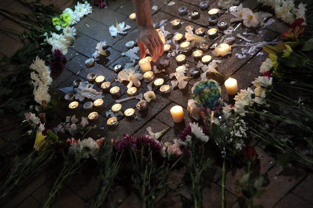 A man tends a makeshift candlelight vigil for those who died or were injured when a car plowed into a crowd of anti-fascist counter-demonstrators marching in Charlottesville, Virginia on August 12, 2017.