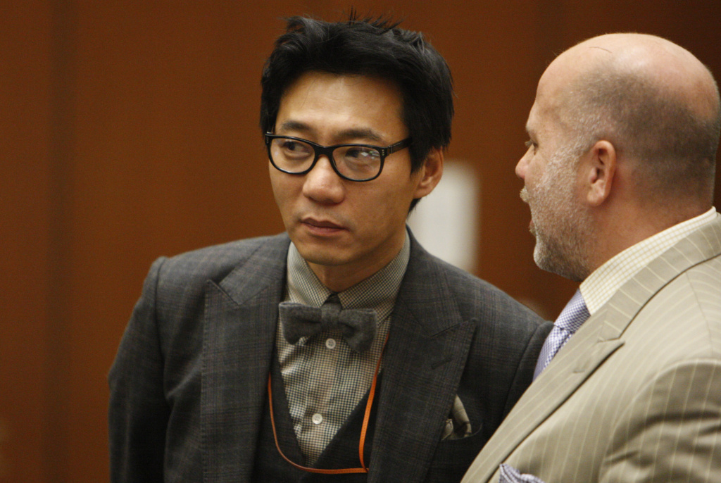 This Jan. 30, 2012 file photo shows Young Lee, one of the former founders of the Pinkberry yogurt chain stands with his attorney Philip Kent Cohen, right, during his arraignment in the Los Angeles Criminal Courts Building in Los Angeles. Lee has been convicted, Friday, Nov. 8, 2013,  of assault with a deadly weapon for striking a transient with a tire iron.