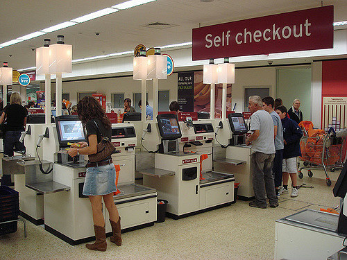 Customers at a store's self-checkout area.
