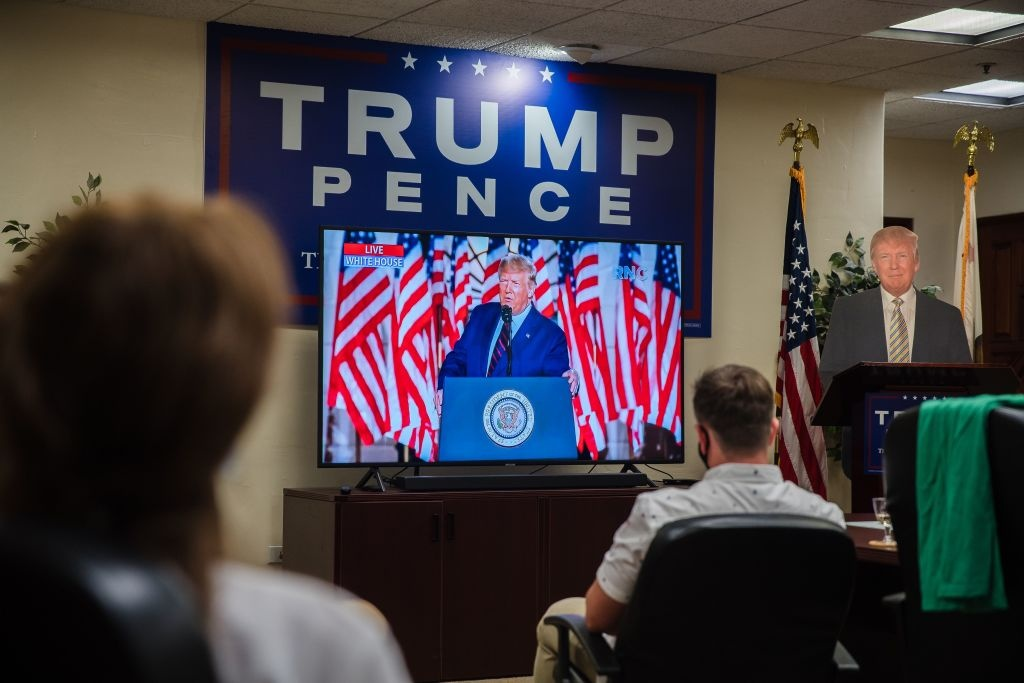 A cardboard cutout of US President Donald Trump stands next to the TV as people watch his acceptance speech for the Republican Party nomination for reelection during the final day of the Republican National Convention in the office of San Diego County's Republican Party in Rancho Bernardo, California on August 27, 2020.