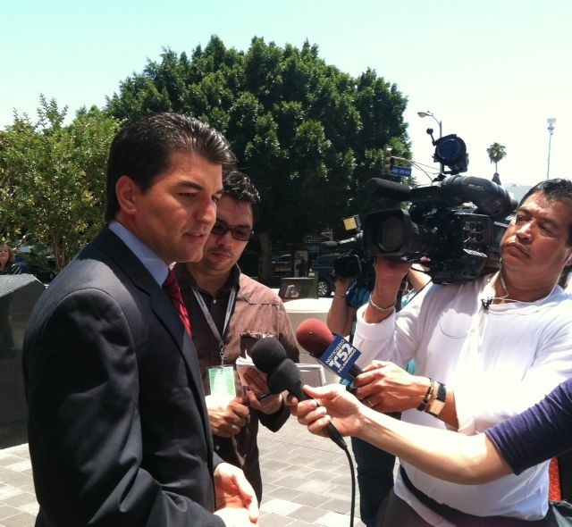 Assistant U.S. Attorney Joseph Akrotirianakis speaks to reporters following the court appearance of three former Cudahy city officials.