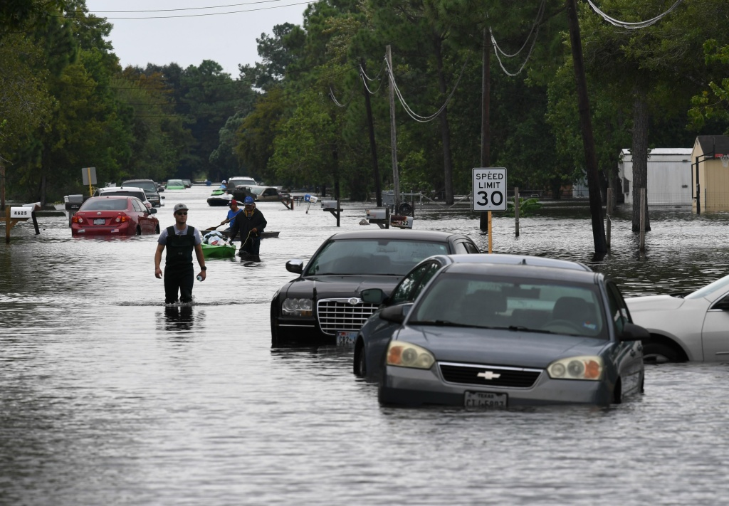 Local residents wade through flooded streets after Hurricane Harvey caused heavy flooding in Crosby, Texas on August 30, 2017.