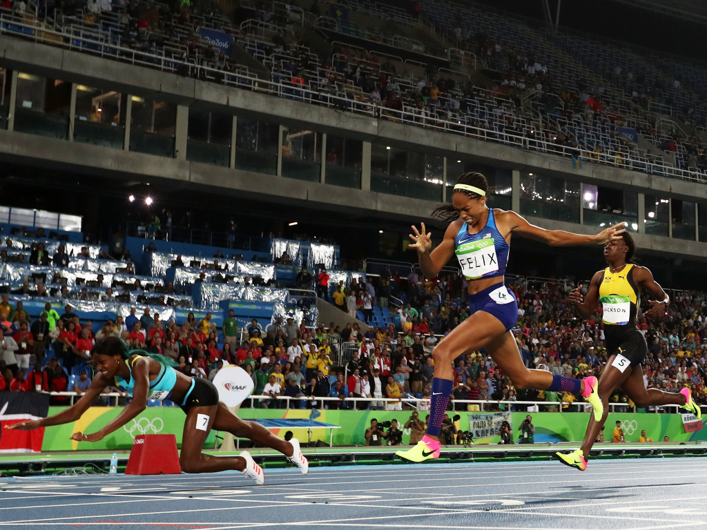 Shaunae Miller of the Bahamas (left) dives over the finish line to win the gold medal in front of Allyson Felix of the U.S., in the women's 400-meter race. Felix won silver; Shericka Jackson of Jamaica (right) won bronze.