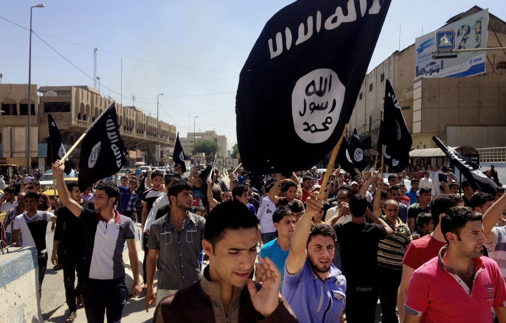 In 2014 photo, demonstrators chant pro-ISIS slogans in front of the provincial government headquarters in Mosul, Iraq.