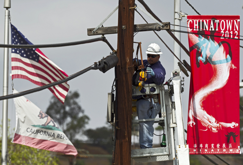 In this March 6, 2012 photo, an AT&T technician works on fiber optic cables used for the expansion of AT&T U-verse Internet service in the Chinatown neighborhood in Los Angeles. Unionized AT&T West workers rejected their contract Thursday. It's possible the workers may strike Saturday.