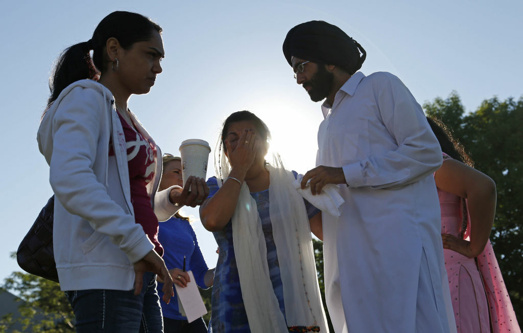 People console each other at the command center near the Sikh Temple of Wisconsin where yesterday a gunman fired upon people at service August, 6, 2012 Oak Creek, Wisconsin.