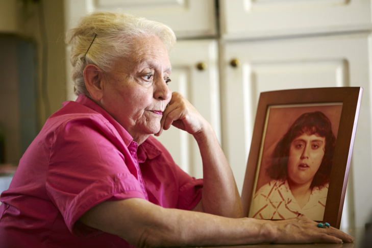 In this May 2, 2014 file photo, Rosemary Verdugo poses with a photo of her late daughter, Mary Ann Verdugo, seen at 17 years-old, at her home in Maywood, Calif. Mary Ann Verdugo died at age 49  of cardiac arrest in a Southern California Target retail store. On Monday, June 23, 2014, the California Supreme Court ruled that large retailers aren't required to have defibrillators on hand to help treat customers and workers who suffer sudden cardiac arrest.