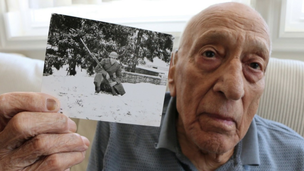 Steve Politis holds a picture of himself from World War Two. Politis was the only man of his 14 man unit to survive the Allied invasion of Sicily.