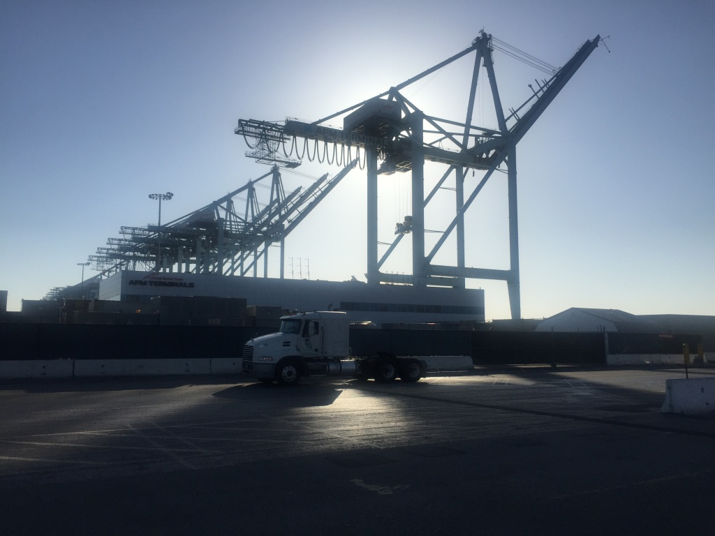 A truck heads into the APM Terminal at the Port of Los Angeles as the sun begins to set