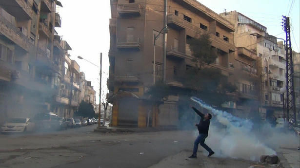 A protester in the flahspoint central Syrian city of Homs throws a tear gas bomb back towards security forces, on Wednesday.
