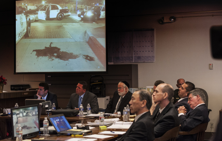 Jurors see an image of a pool blood left after Fullerton police arrested Kelly Thomas in 2011 as officers Manuel Ramos, second from right, and Jay Cicinelli, second from left, listen during opening statements in their trail.