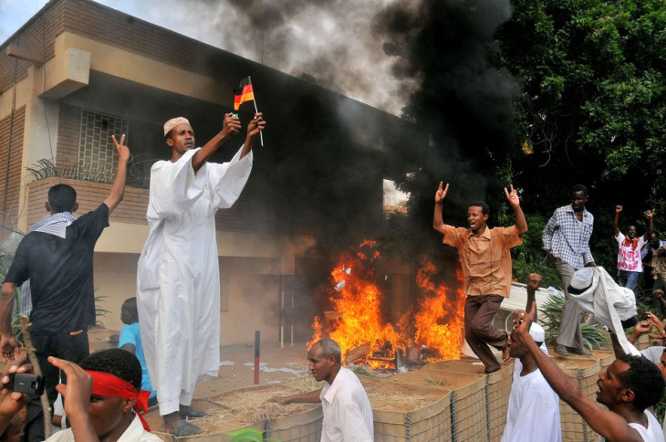 A Sudanese demonstrator burns a German flag as others shout slogans after torching the German embassy in Khartoum during a protest against a low-budget film mocking Islam on Sep. 14. Around 5,000 protesters in the Sudanese capital angry over the amateur anti-Islam film stormed the embassies of Britain and Germany, which was torched and badly damaged.