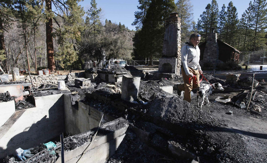 Rick Heltebrake with his dog Suni looks over the burned-out cabin where Christopher Dorner's remains were found after a police standoff Tuesday near Big Bear, Calif., Friday Feb. 15, 2013. Earlier, Heltebrake had been carjacked by Dorner.
