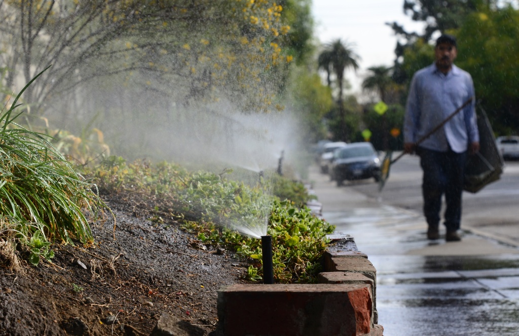 A gardener walks past a row of sprinklers watering plants and foliage in front of an apartment complex in South Pasadena, California on Jan. 21, 2014.