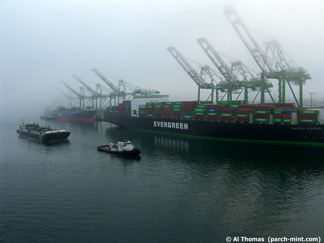 A tugboat pulls a barge through the Port of Los Angeles on a foggy morning.