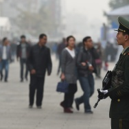 Chinese paramilitary police officers watch over pedestrians in the Wangfujing shopping district in Beijing.