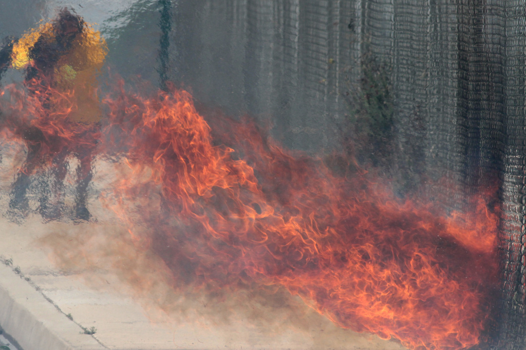 Flames from the wind driven Etiwanda fire burn through a fence on April 30, 2014 in Rancho Cucamonga.