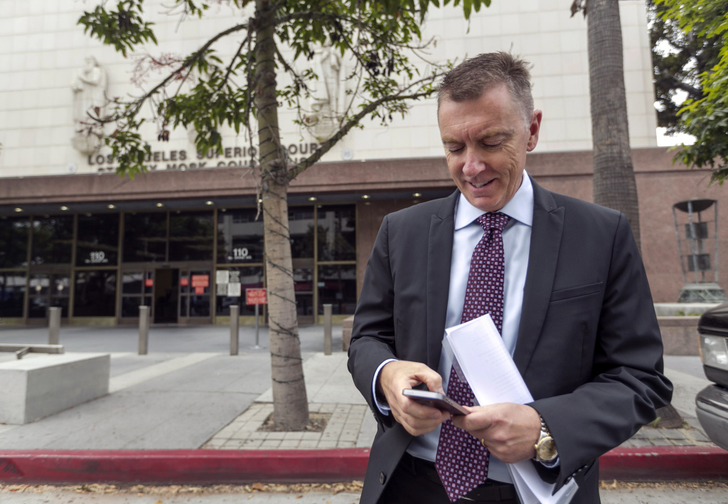In this June 10, 2014, photo, Los Angeles Unified School District Superintendent John Deasy checks his phone outside the Stanley Mosk Courthouse, before the verdict in the Vergara v. California lawsuit in Los Angeles. Days after a judge found California's teacher tenure laws unconstitutional, a bill making it easier to fire abusive educators heads to Gov. Jerry Brown.