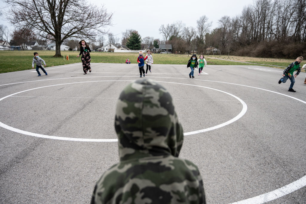 A child moderates a game of Red Light Green Light to others during recess on the playground of Medora Elementary School on March 17, 2021 in Louisville, Kentucky.