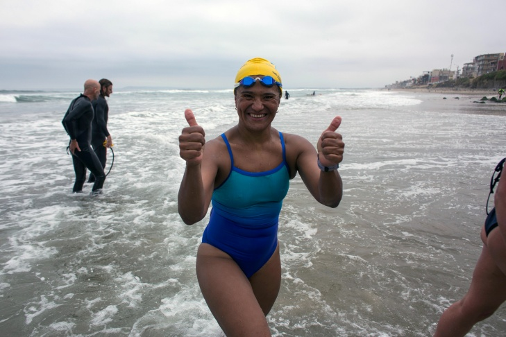 Mexican swimmer Nora Toledo, participating in the Pan-American Colibri Crossing, celebrates upon arrival to the beach in Playas de Tijuana, Mexico on May 5, 2017, after swimming across the US-Mexico marine border from Imperial Beach in San Diego, California. Twelve swimmers from five countries participated in the Pan-American Colibri Crossing, a cross-border U.S.-Mexico swim that aims to raise awareness and raise funds for the Colibri Center for Human Rights, which supports migrants' human rights. / AFP PHOTO / GUILLERMO ARIAS        (Photo credit should read GUILLERMO ARIAS/AFP/Getty Images)
